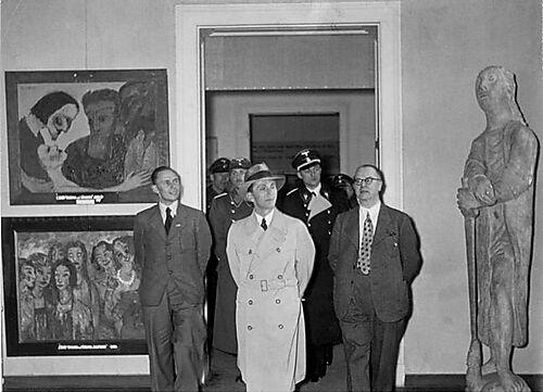 """Fotografie, Joseph Goebbels in der Ausstellung """"Entartete Kunst"""", 1938 Berlin. Links zwei Gemälde von Emil Nolde"""