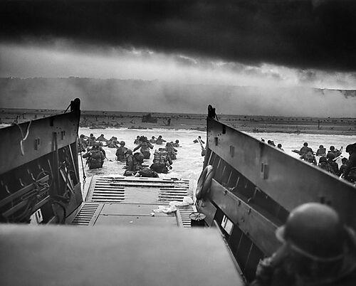 Fotografie oben: Taxis to Hell – and Back – Into the Jaws of Death, von Robert F. Sargent, CPhoM,Amerikanische Invasoren springen von der Rampe eines Landungsbootes
